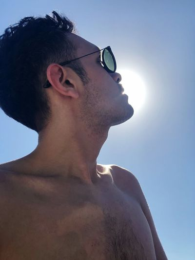 Low angle view of shirtless man against clear sky