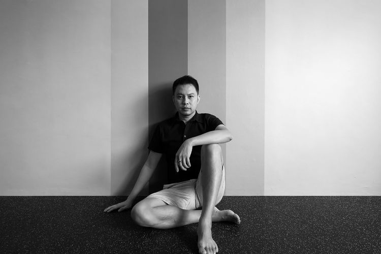 Portrait of young man sitting against wall at home