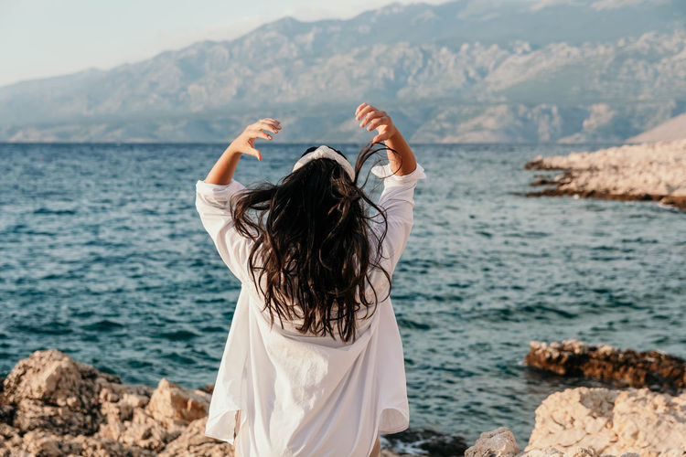 Rear view of young woman in white shirt on beach. long hair, hairstyle, lifestyle.