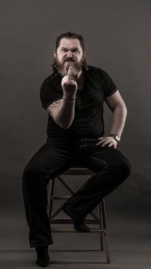 Mid Adult Man Gesturing Obscene Gesture While Sitting Against Black Background
