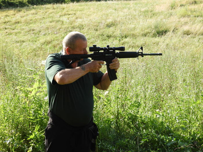 Senior man using rifle while standing on field