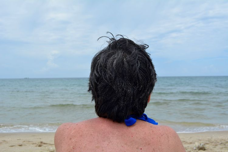 Rear view of mature woman looking at sea while sitting on beach against sky