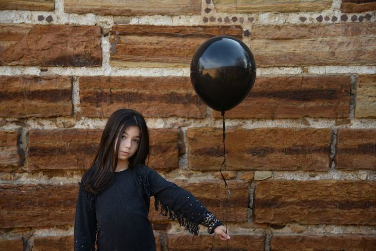 Girl playing with balloon against stone wall
