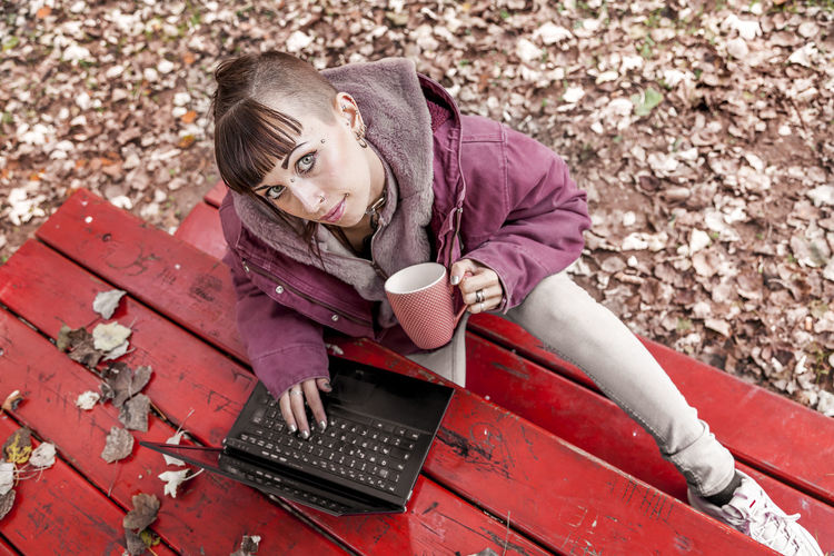 High Angle Portrait Of Young Woman Using Laptop On Table While Sitting In Park