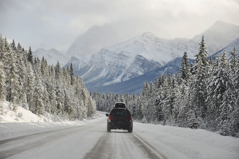 Road amidst snowcapped mountains against sky during winter