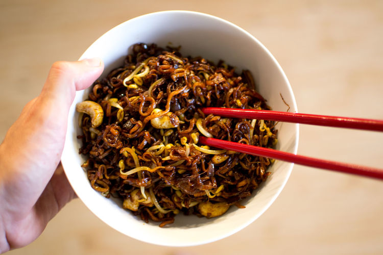 Bowl Brown Cashew Chopsticks Close-up Focus On Foreground Food Freshness Fried Healthy Eating Holding Human Finger Lifestyles Meal Noodles Nuts Ready-to-eat Red Serving Size Soy