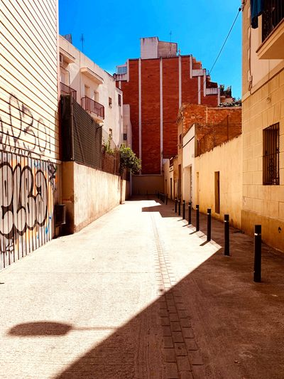 Footpath amidst buildings in city on sunny day