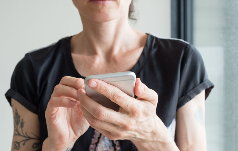 Midsection Of Woman Using Phone