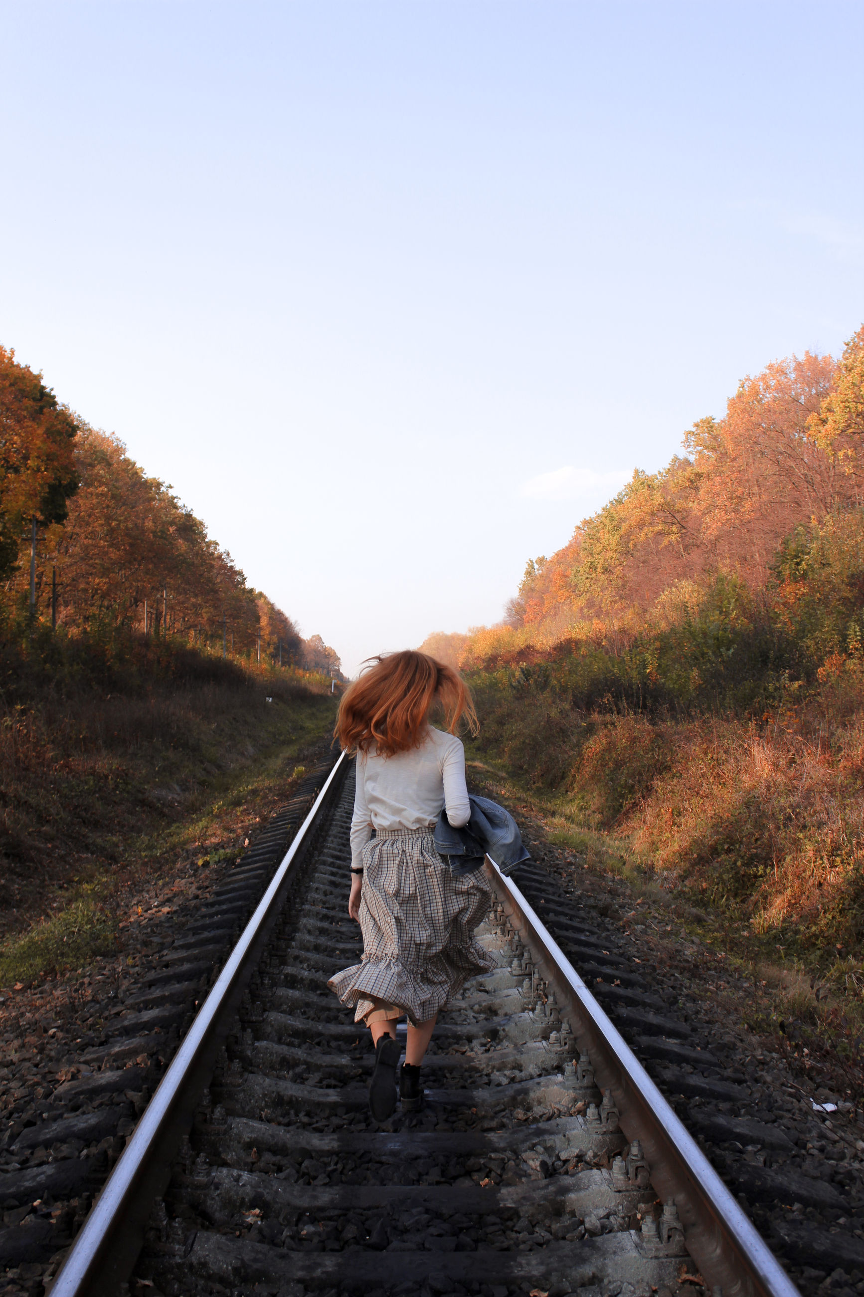 one person, tree, railroad track, sky, rail transportation, track, full length, the way forward, direction, real people, nature, leisure activity, rear view, lifestyles, plant, transportation, casual clothing, day, women, walking, hairstyle, outdoors, change, diminishing perspective
