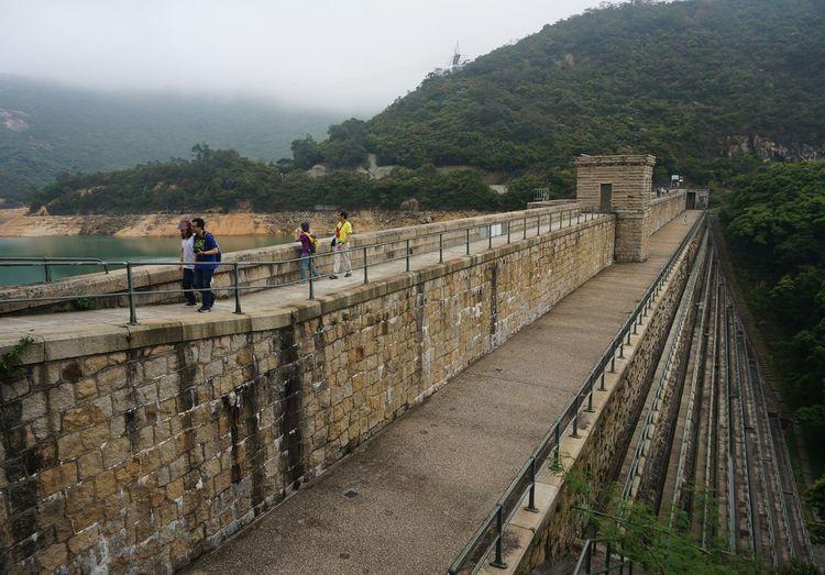 People walking on bridge against mountains