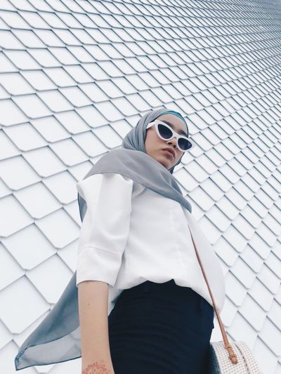 Portrait of woman wearing sunglasses and hijab while standing against wall
