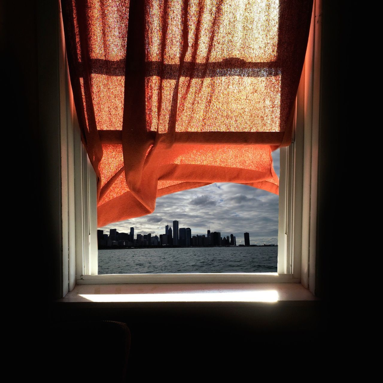 Window with red curtain looking to the city of skyscrapers