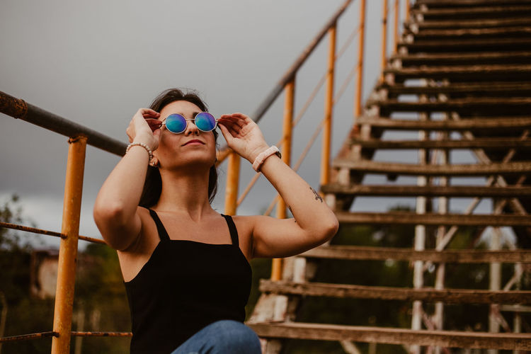 Young woman in sunglasses sitting against steps