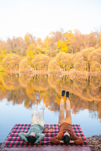 Rear view of people sitting by lake during autumn