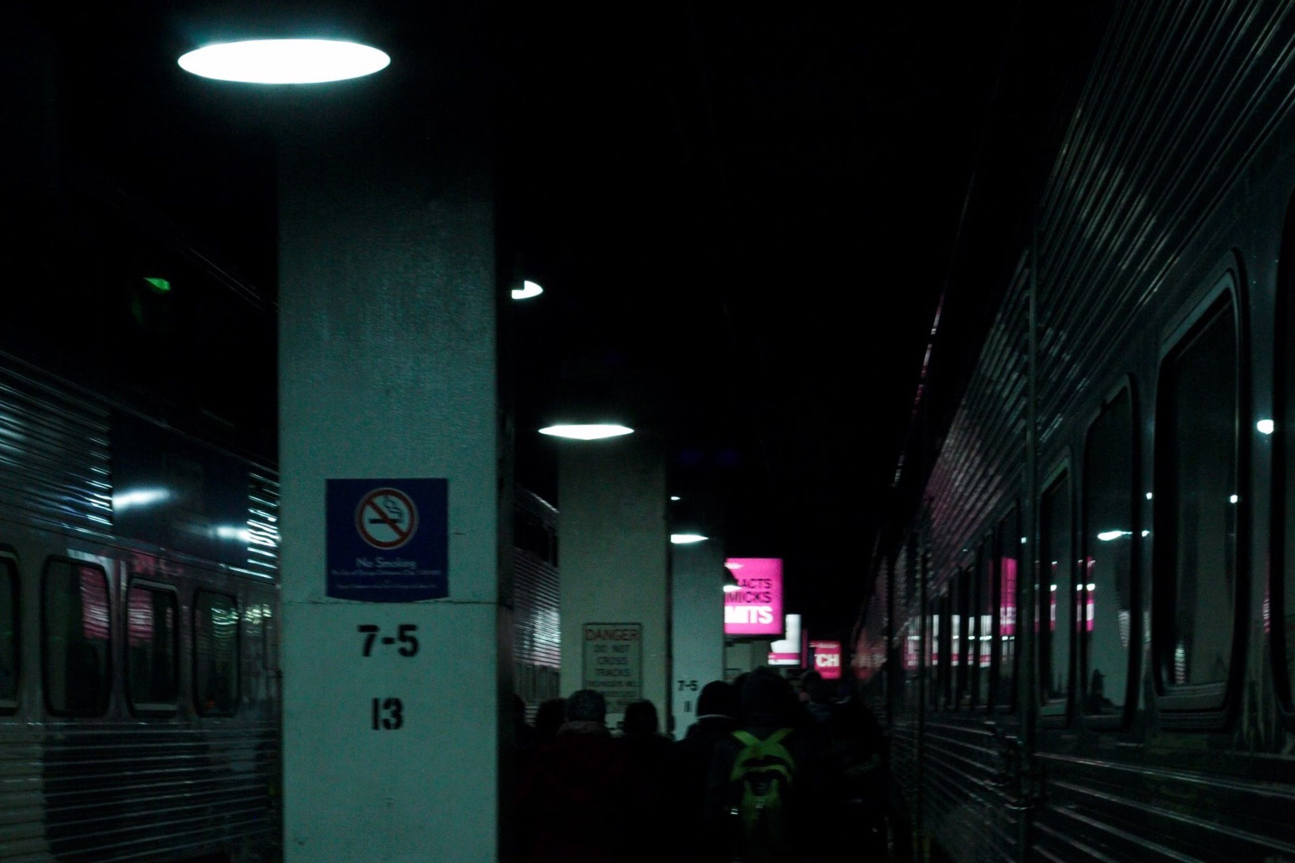 illuminated, night, architecture, built structure, lighting equipment, transportation, indoors, railroad station, text, subway station, railroad station platform, public transportation, incidental people, ceiling, city, western script, the way forward, building exterior, non-western script, city life