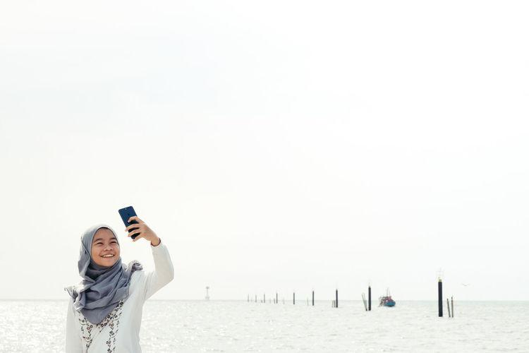 Teenage girl taking selfie from mobile phone by sea
