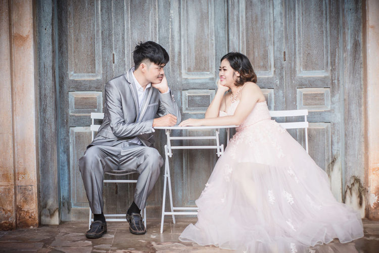 Two People Women Adult Emotion Sitting Celebration Wedding Event Young Adult Happiness Newlywed Couple - Relationship Bride Wedding Dress Togetherness Full Length Love Smiling Young Women Husband Wife