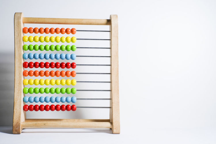 Close-up of multi colored abacus against gray background