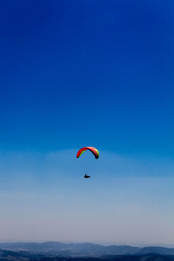 Person paragliding over sea against blue sky