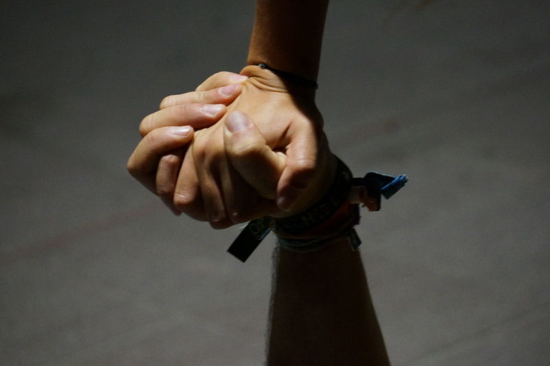 Cropped Image Of Friends Holding Hands At Footpath