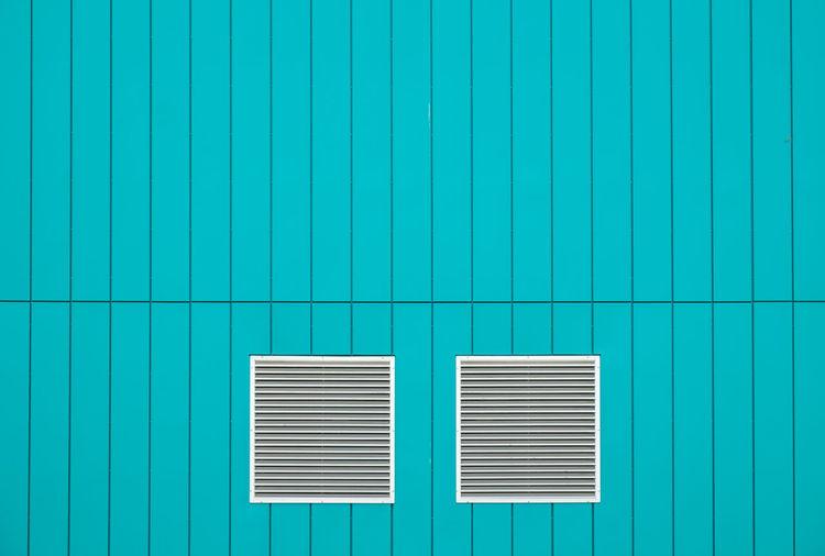 Windows on turquoise wall