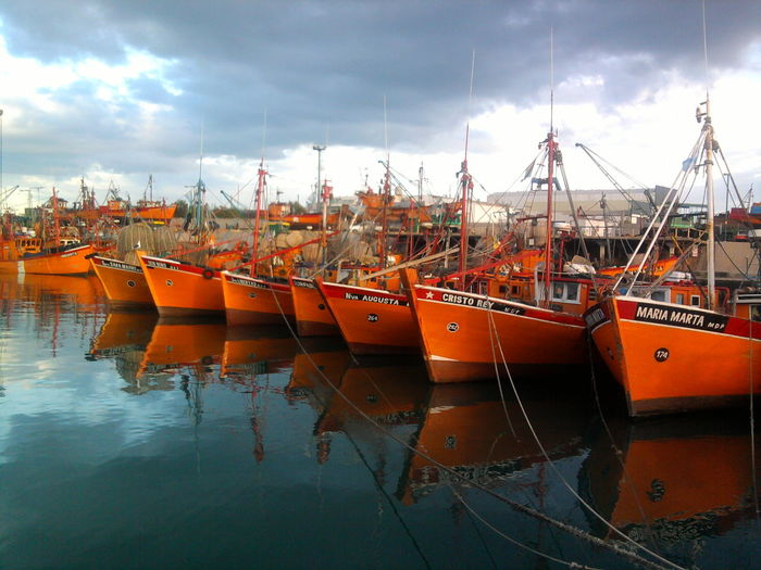 Orange Boats Moored At Harbor Against Cloudy Sky