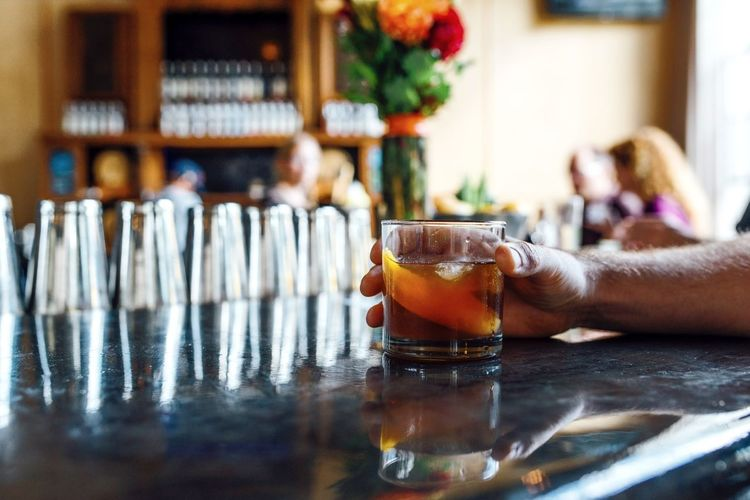 Cropped hand of man having alcohol at bar counter