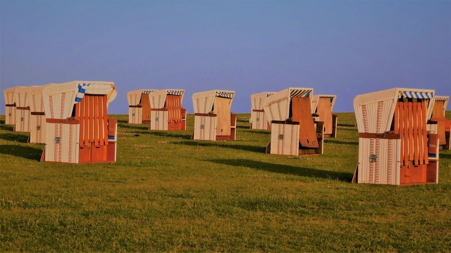 Hooded chairs on field against clear blue sky