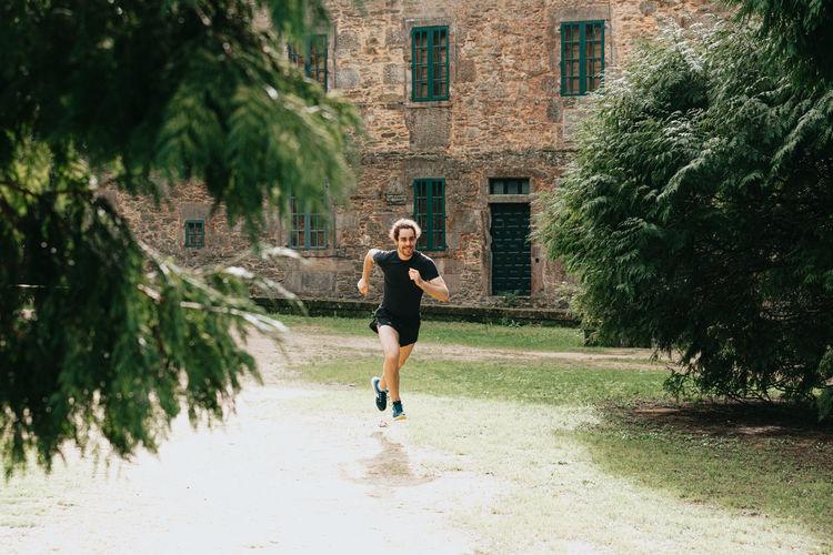 Full length of man running against building