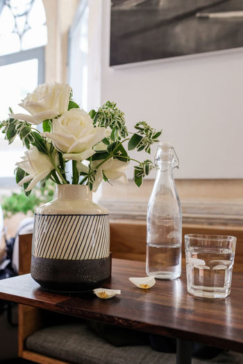 White roses in a black and white ceramic vase and glass bottle of water and aglass of water on a wooden table in day light with blurred background Beauty In Nature Bouquet Close-up Container Flower Flower Arrangement Flower Head Flowering Plant Focus On Foreground Fragility Freshness Glass - Material Indoors  Nature No People Petal Place Mat Plant Roses Still Life Table Vase Vulnerability  Wood - Material