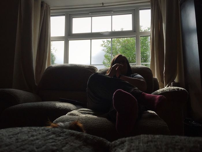 Low angle view of woman relaxing on sofa at home