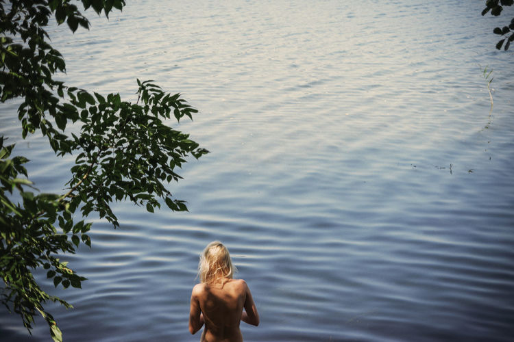 Rear view of topless woman standing in lake