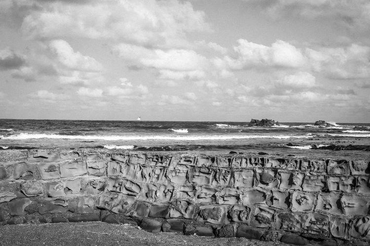 Text on beach against sky