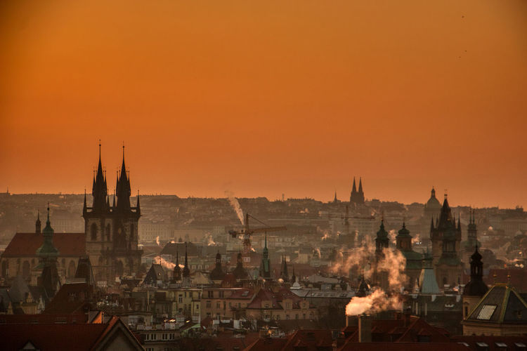 Prague silhouette at morning sunrise with red sky and chimney smoke