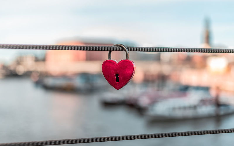 Close-up of padlock on railing against townscape
