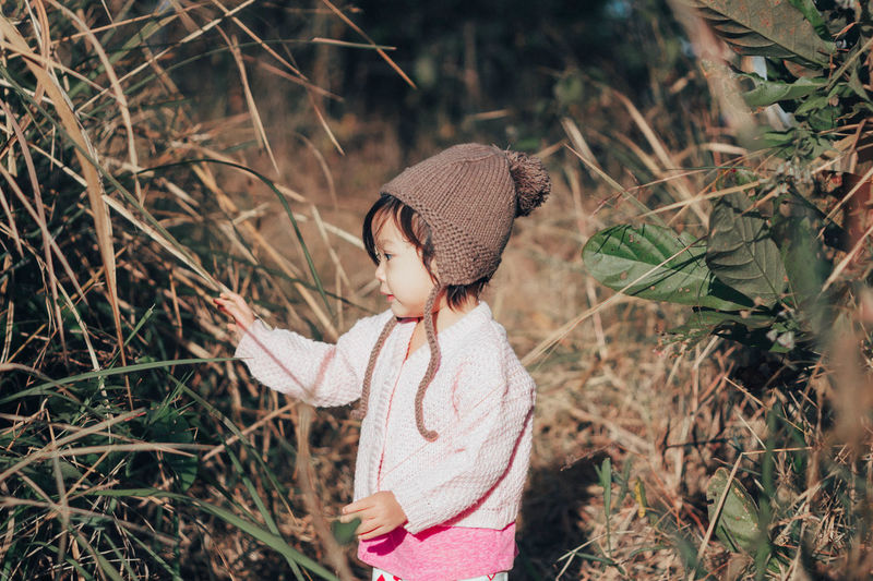 Childhood Child One Person Clothing Land Plant Hat Nature Standing Leisure Activity Women Casual Clothing Day Real People Waist Up Girls Focus On Foreground Field Lifestyles Innocence Outdoors Hairstyle