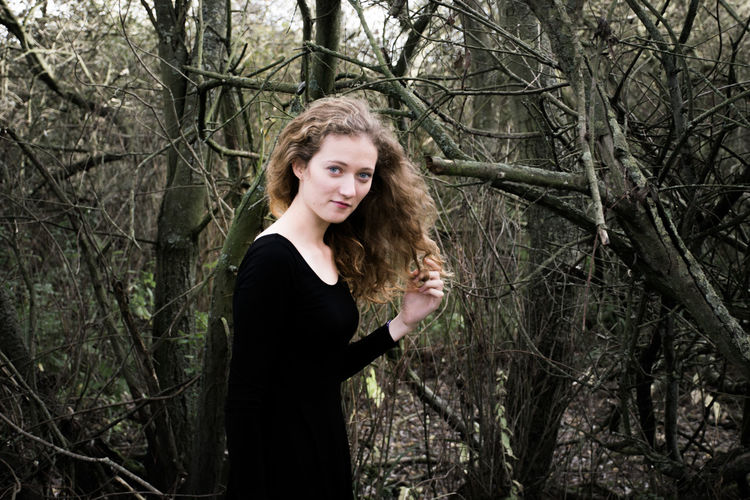 Branch Casual Clothing Day Dry Focus On Foreground Forest Front View Long Hair Looking At Camera Natural Light One Person Outside Portrait Side View Smiling Twig Young Adult Young Woman Picturing Individuality