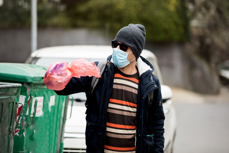 Man with mask holding garbage standing on street