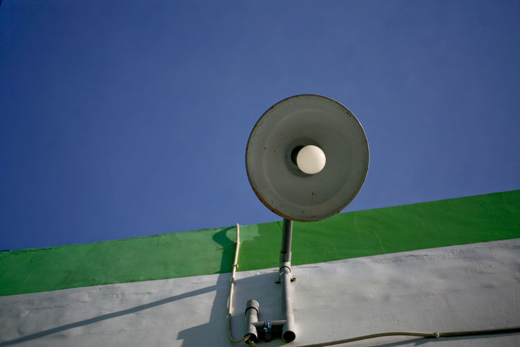 Low angle view of electric lamp against blue sky