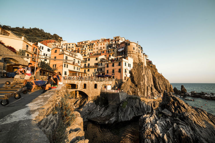 Houses on rock formation at manarola against clear sky