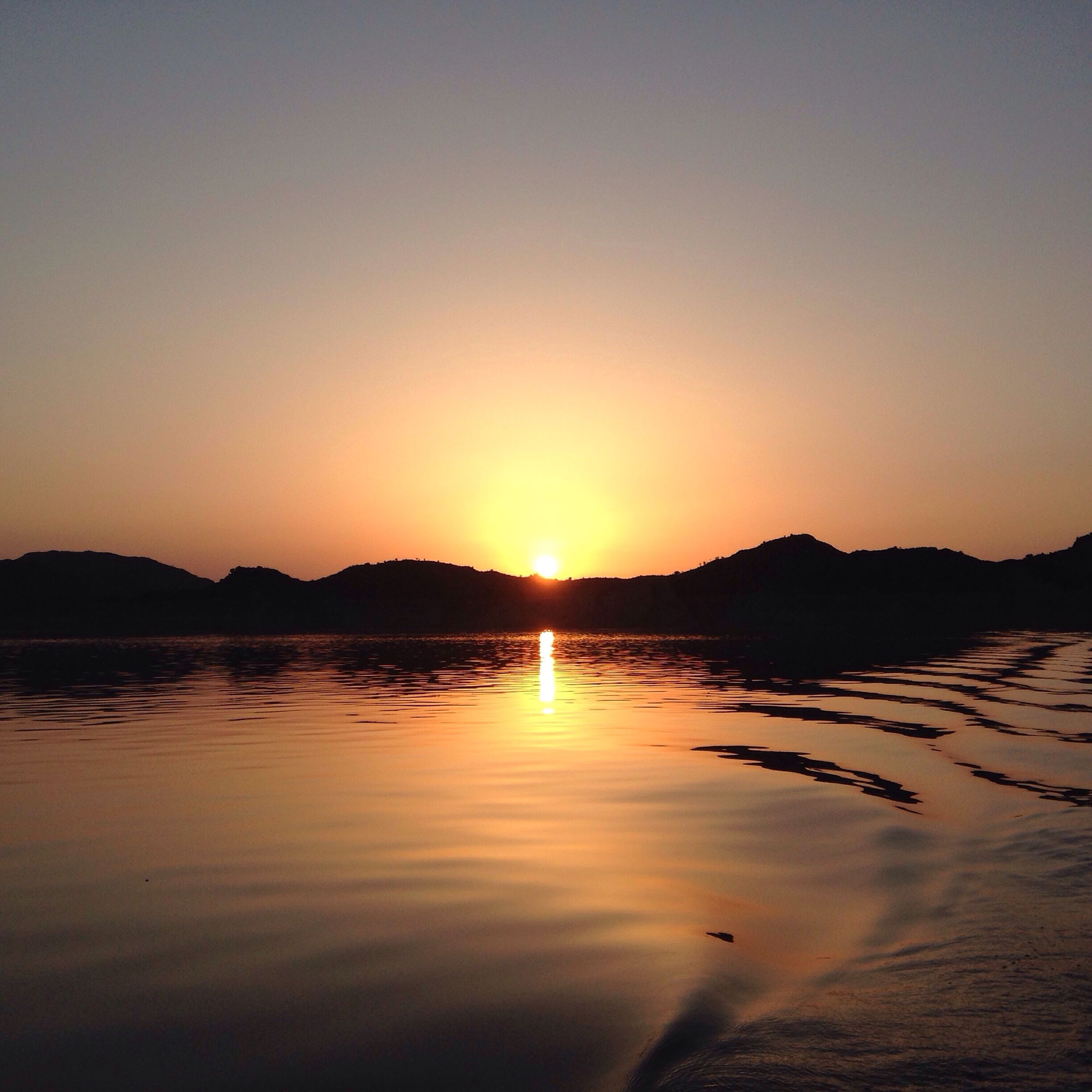 sunset, water, reflection, scenics, tranquil scene, tranquility, sun, clear sky, beauty in nature, mountain, orange color, sea, waterfront, nature, majestic, calm, non-urban scene, vacations, tourism, no people, mountain range, remote, romantic sky, vibrant color, water surface