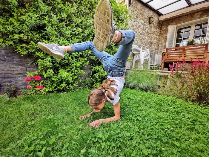Upside down image of father and daughter on grass in yard
