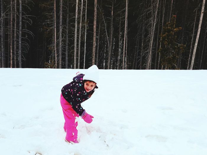 Girl Playing With Snow Against Trees