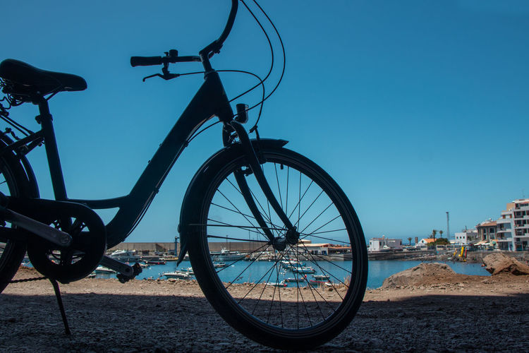 Bicycle by street against clear blue sky