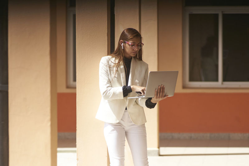 Young businesswoman using smartphone while standing outdoors