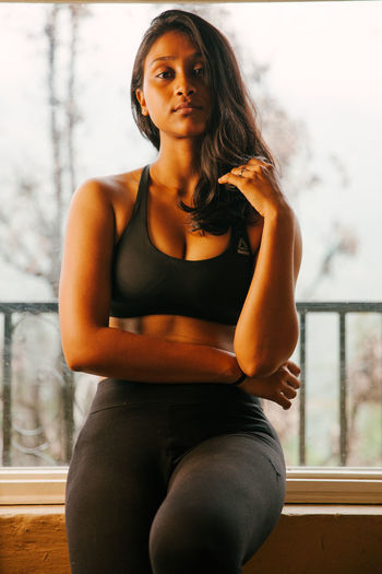 Portrait of a girl in black sport outfit against a glass window in the Himalayas. Looking At Camera Beautiful Woman Young Women Front View Portrait Lifestyles Women Portrait Of A Woman Portrait Of A Girl Sporty Girl Sportsbra