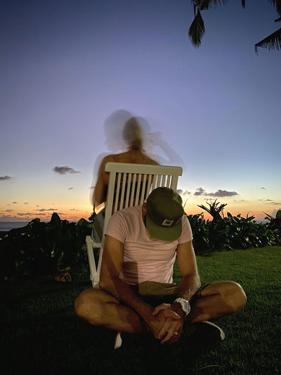 Rear view of couple sitting on field against sky during sunset
