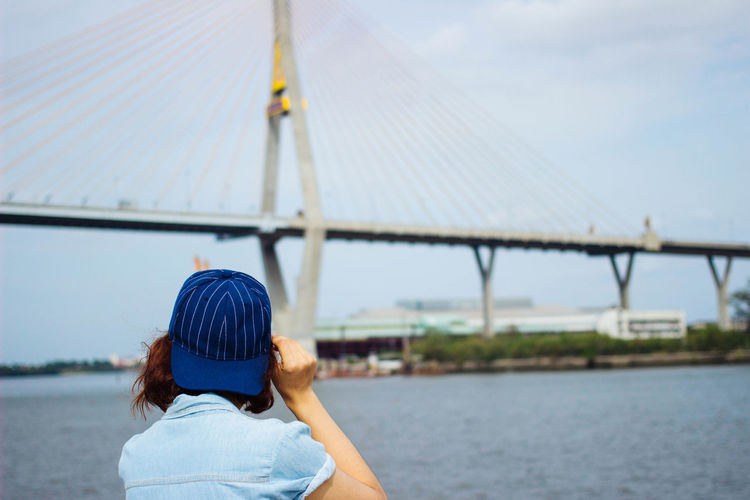 woman back touching cap standing in front of bridge Adult Architecture Back Bridge - Man Made Structure Built Structure Casual Clothing Connection Day Focus On Foreground Headshot Leisure Activity Lifestyles Nature Nautical Vessel Outdoors People Real People Rear View River Sky Thailand Transportation Water Women