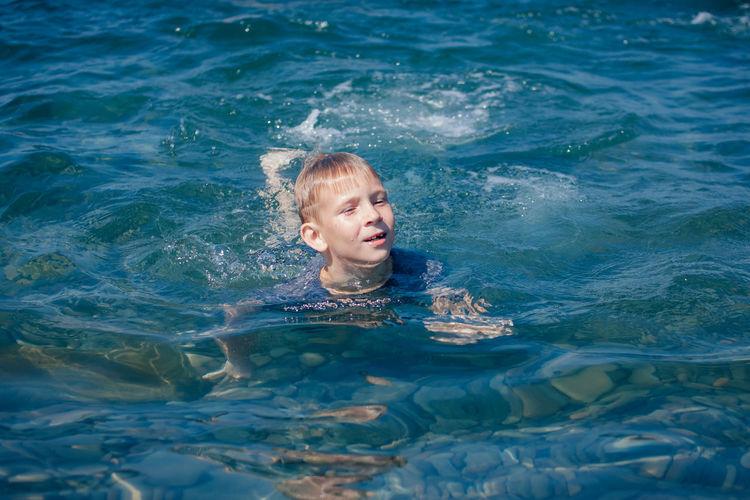 Boy swimming in lake