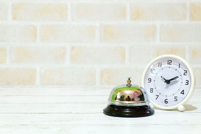 Ring bell and white table clock on a table. Copy space for text and logo. Object Backgrounds Copy Space Ring Bell Bell Alarm Front Counter Front Desk Office Ting Ring Metal Time Clock Indoors  No People Minute Hand Clock Face Close-up Day